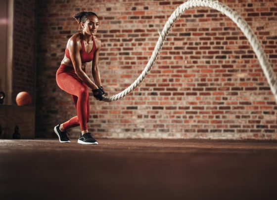 Woman using training rope for exercise at gym. Athlete working out with battle rope at cross training gym.